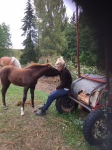 Foto på Sanna som gosar med sin häst.